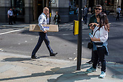 A male City worker carries a long box across Threadneedle Street in the City of London, the capital's financial district (aka the Square Mile), on 22nd August 2019, in London, England.