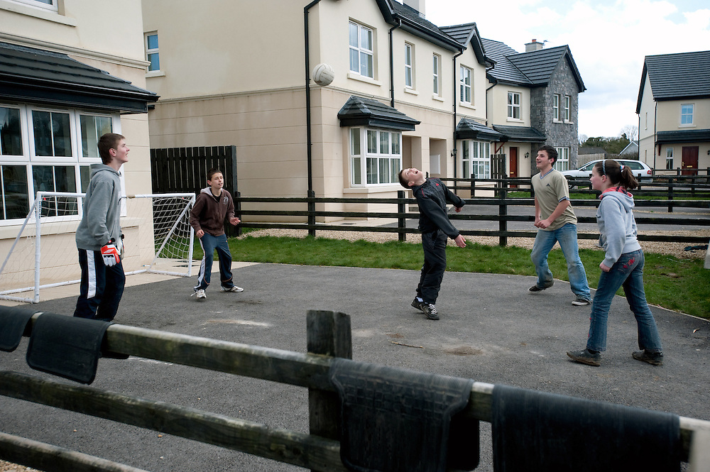 Aisling Maguire and her friends play football in the fromt garden of an empty house in Woodford Green, Newtowngore, Co. Leitrim.  Of 23 houses in the development, only 7 are occupied. The Semi detatched houses in the development were priced at EUR240,000 in 2006 and can now be bought for EUR130,000.