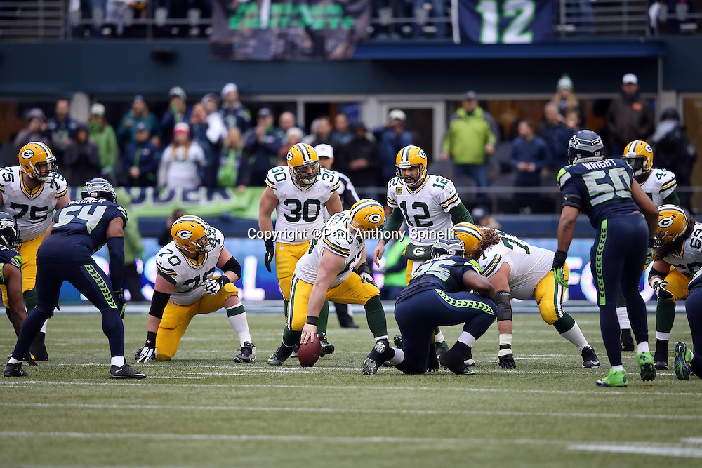 Green Bay Packers center Corey Linsley (63) looks back as he communicates with Green Bay Packers quarterback Aaron Rodgers (12) during the NFL week 20 NFC Championship football game against the Seattle Seahawks on Sunday, Jan. 18, 2015 in Seattle. The Seahawks won the game 28-22 in overtime. ©Paul Anthony Spinelli