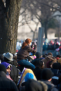A young woman sits on her friend's shoulders to get a better photograph of the Capitol during President Barrack Obama's inauguration.