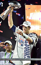 New England Patriots quarterback Tom Brady lifts the Vince Lombardi Trophy.<br />