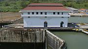 Edificación de 1913 del Canal de Panamá en Miraflores, Ciudad de Panamá,..El Canal de Panamá mide 80 Kilómetros de largo.Su cauce discurre entre el Atlántico y el Pacifico. El Canal esta conformado por varios elementos: el lago Gatún;el Corte Culebra; y las esclusas(Miraflores y Pedro Miguel en el Pacifico; y Gatún en el Atlántico)..El canal utiliza un sistema de esclusas:compartimientos con puertas de entrada y salida. Las esclusas funcionan como elevadores de agua:suben la nave desde el nivel del mar( ya sea pacífico o del Atlántico) hacia el nivel del Lago Gatún (26 metros sobre el nivel del mar) así los buques navegan a tráves del cauce del Canal en la Cordillera Central de Panamá.