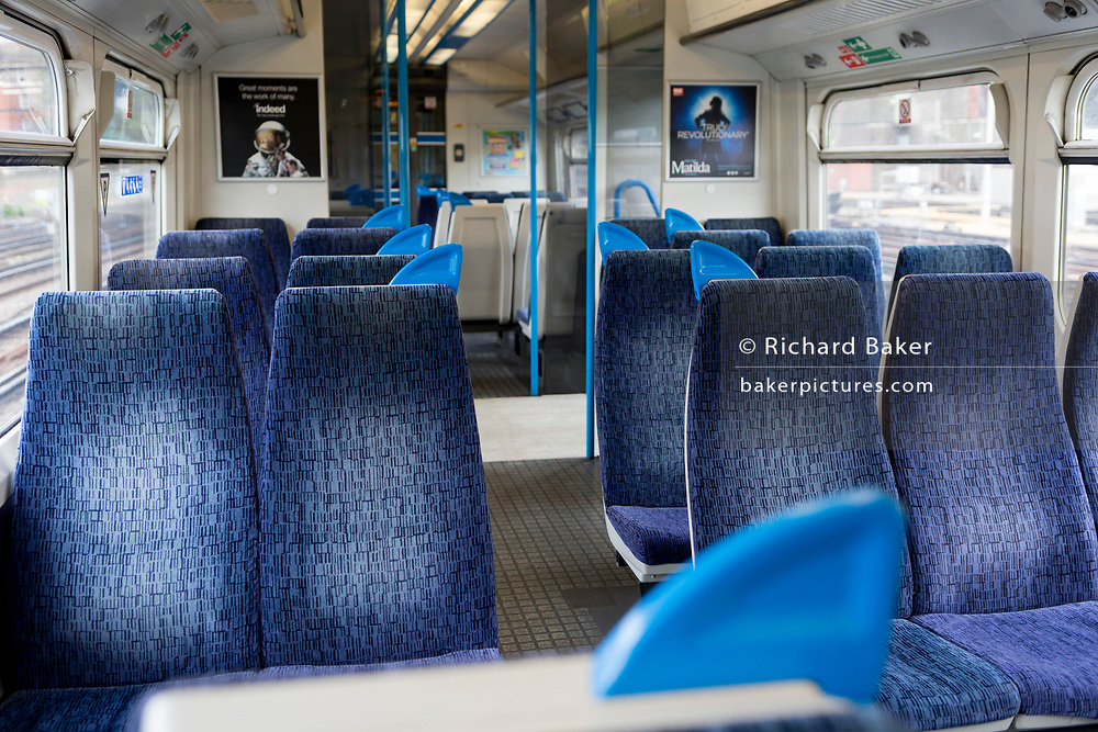 """The UK Chancellor Rishi Sunak has said today it is """"very likely"""" the UK is in a """"significant recession"""" due to the Coronavirus pandemic lockdown, as figures show the economy contracting at the fastest pace since the financial crisis. Empty seats in a train carriage travelling through south London towards Victoria station, on 13th May 2020, in London, England."""