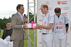 HRH THE DUKE OF CAMBRIDGE receives a gift for Princess Charlotte from ANDRE KONSBRUCK Director of Audi UK at the Audi Polo Challenge at Coworth Park, Blacknest Road, Ascot, Berkshire on 31st May 2015.