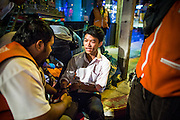 "30 NOVEMBER 2012 - BANGKOK, THAILAND:  Volunteer medics with the Ruamkatanyu Foundation treat a man injured in a motorcycle accident during a Friday night shift. The Ruamkatanyu Foundation was started more than 60 years ago as a charitable organisation that collected the dead and transported them to the nearest facility. Crews sometimes found that the person they had been called to collect wasn't dead, and they were called upon to provide emergency medical care. That's how the foundation medical and rescue service was started. The foundation has 7,000 volunteers nationwide and along with the larger Poh Teck Tung Foundation, is one of the two largest rescue services in the country. The volunteer crews were once dubbed Bangkok's ""Body Snatchers"" but they do much more than that now.   PHOTO BY JACK KURTZ"