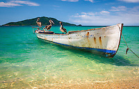 A weathered fisherman's skiff floats in the shallows of the Caribbean in front of Cayos Cochinos off the coast of Honduras