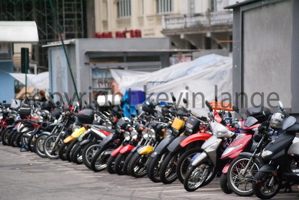 a row of motorcycles parked along the street in rio de janeiro, brazil.