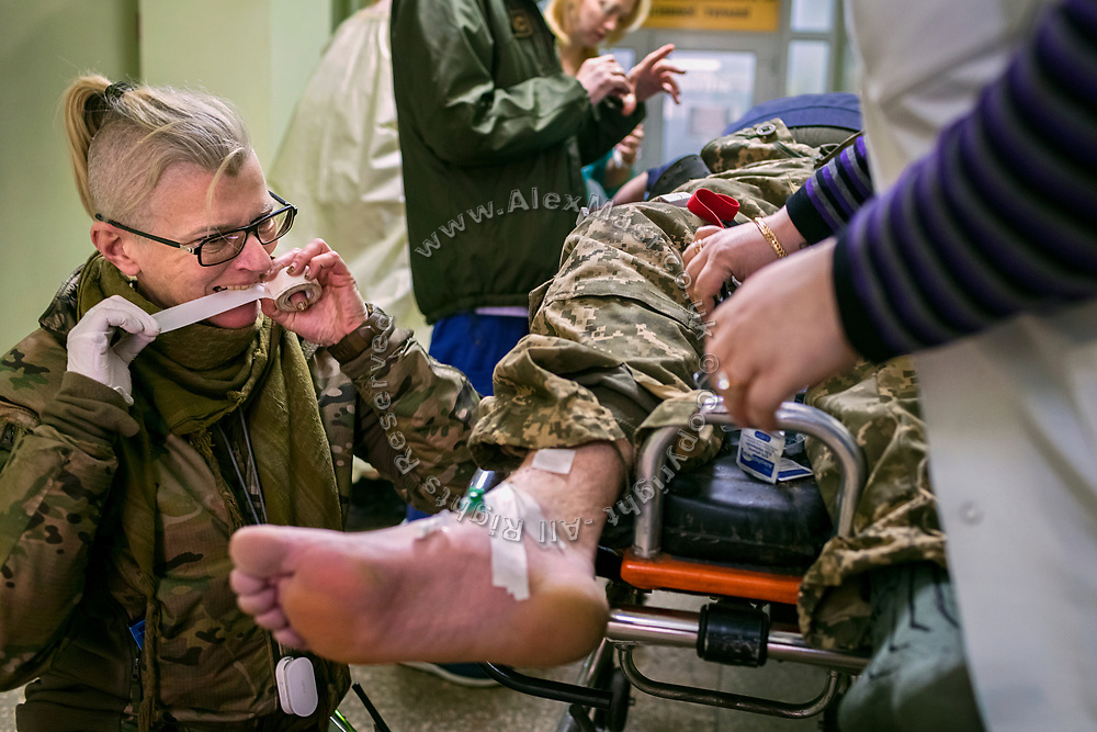 Julia Paevska is assisting a solder that fell on a sharp glass and wounded his left leg, inside the hospital in Bakhmut, a town in eastern Ukraine's conflict zone.