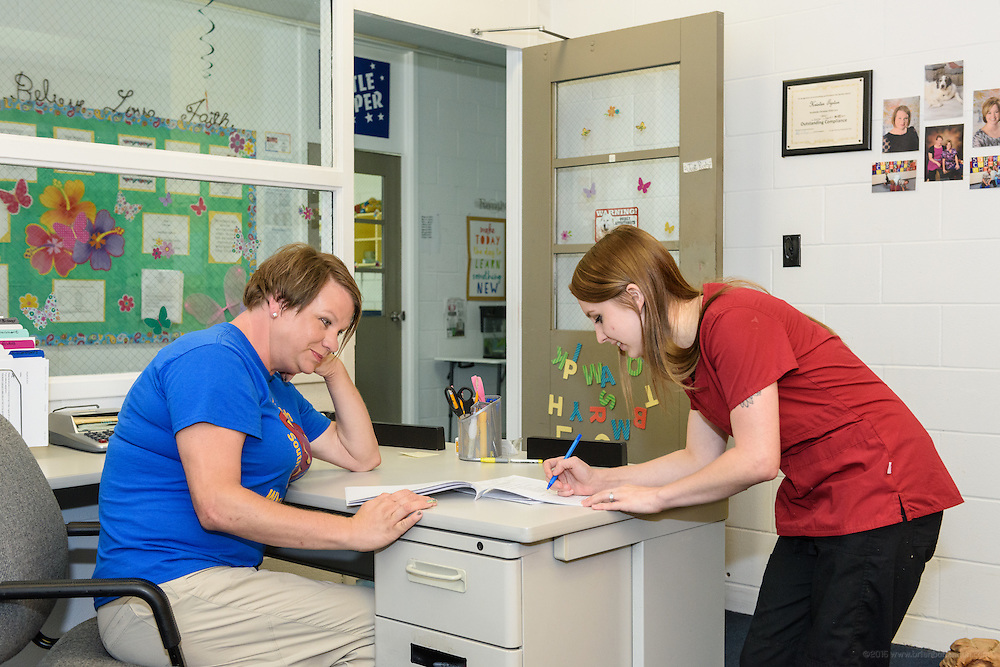 Kristen Tipton, left, director at Southside Christian Child Care Day Care Center at10315 Deering Road in Valley Station, helps new teacher Shelby Alford with her paperwork as she begins her first day. (Photo by Brian Bohannon)