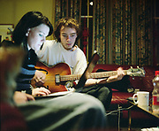 Kayleigh on the laptop and Chris playing bass guitar, UK, 2000s.