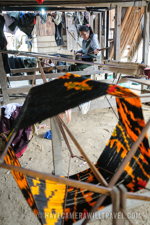 A woman using her loom on the dirt floor under her house in northeastern Laos. At right, in the foreground, is some of the brightly dyed silk thread she's using, and at bottom right you can see part of a bicycle wheel that has been repurposed for part of the spindle.