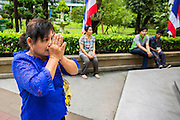 26 NOVEMBER 2012 - BANGKOK, THAILAND:  A woman prays for the hospitalized King in the courtyard at Siriraj Hospital, outside the wing housing the King of Thailand, in Bangkok. Siriraj was the first hospital in Thailand and was founded by King Chulalongkorn in 1888. It is named after the king's 18-month old son, Prince Siriraj Kakuttaphan, who had died from dysentery a year before the opening of the hospital. It's reported to one of the best hospitals in Thailand and has been home to Bhumibol Adulyadej, the King of Thailand, since 2009, when he was hospitalized to treat several ailments. Since his hospitalization tens of thousands of people have come to pay respects and offer get well wishes. The King's 85th birthday is on Dec 5 and crowds at the hospital are growing as his birthday approaches. The King is much revered throughout Thailand and is seen as unifying force in the politically fractured country.       PHOTO BY JACK KURTZ