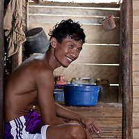 A man sits in a doorway in his modest home in Teku, Central Sulawesi