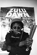 Black militant John Taylor poses in front of a poster for the movie 'Zulu Dawn', London, UK, 1987