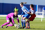 Brighton defender Amy Taylor gets the ball to her keeper Faye Baker whilst shielding Charlton's Emma Harrison during the FA Women's Premier League Cup quarter-final match between Brighton Ladies and Charlton Athletic WFC at The American Express Elite Football Performance Centre, Lancing, United Kingdom on 1 March 2015. Photo by Geoff Penn.