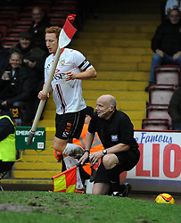 Milton Keynes Dons' Dean Lewington take stye linesman out as he can't avoid sliding off the pitch - Photo mandatory by-line: Joe Meredith/JMP - Tel: Mobile: 07966 386802 18/01/2014 - SPORT - FOOTBALL - Ashton Gate - Bristol - Bristol City v MK Dons - Sky Bet League One