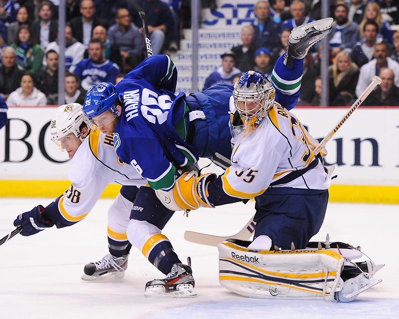 VANCOUVER, CANADA - DECEMBER 1: Jannik Hansen #36 of the Vancouver Canucks flies into Pekka Rinne #35 of the Nashville Predators during the second period at Rogers Arena on December 1, 2011 in Vancouver, British Columbia, Canada. (Photo by Derek Leung/Getty Images)