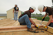 Nicor Inc. welder Bill Pickering (C) works with his son James (R) at a Habitat for Humanity home-building site in West Chicago, Illinois on Saturday, May 21st, 2011 during Nicor's 15th Volunteer Day. The company's annual event includes volunteering at events like outdoor clean ups at local social service agencies, food sorting at area pantries and energy-saving improvements at the homes of senior citizens. For additional information, visit nicor.com or contact Richard Caragol at 630-388-2686.