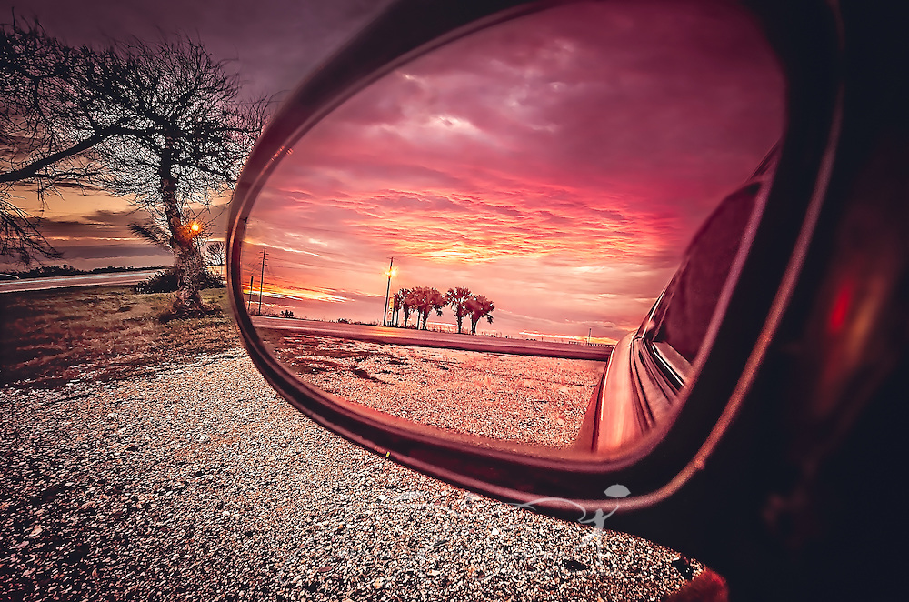 The sunset is reflected in a car mirror, January 7, 2016, at Cedar Point near Dauphin Island, Alabama. (Photo by Carmen K. Sisson/Cloudybright)