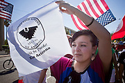 Apr. 19, 2009 -- PHOENIX, AZ: A woman carries a United Farm Workers flag during a march in central Phoenix Sunday. About 2,000 people marched from the Arizona State Capitol to Cesar Chavez Plaza in downtown Phoenix. The march was organized by the United Farm Workers of America to promote immigration reform.  Photo by Jack Kurtz
