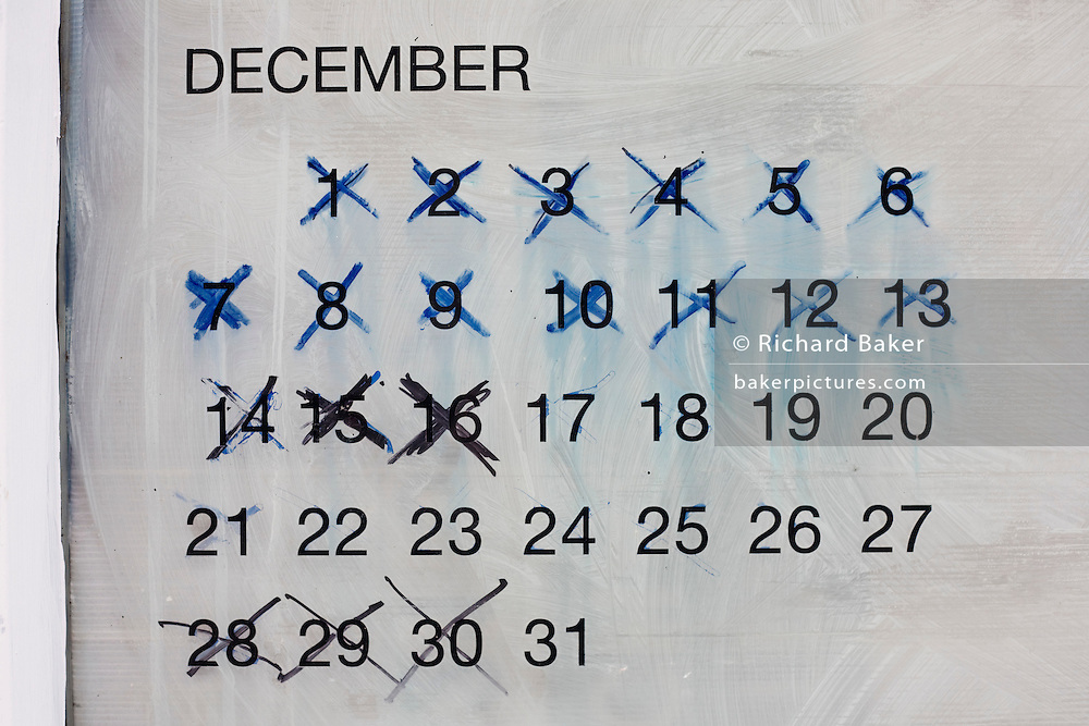 The last days of 12th month December, have been crossed off as a countdown to the end of a year, written on a shop window.