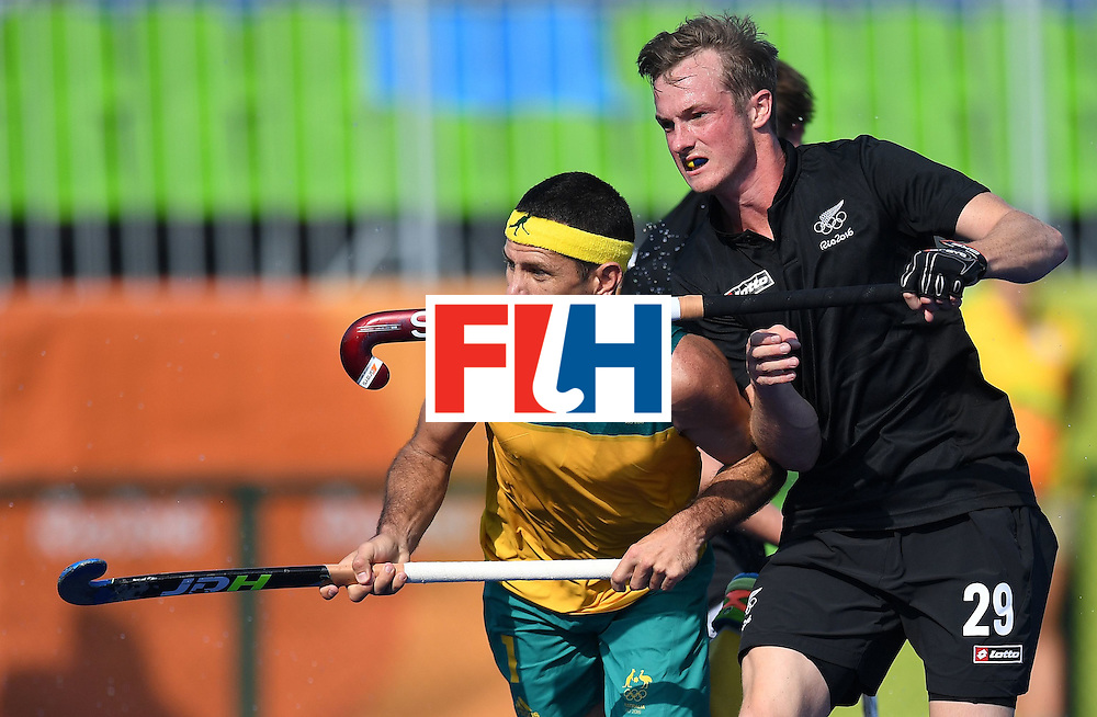 New Zealand's Hugo Inglis (R) pushes Australia's Jamie Dwyer during the men's field hockey Australia vs New Zealand match of the Rio 2016 Olympics Games at the Olympic Hockey Centre in Rio de Janeiro on August, 6 2016. / AFP / MANAN VATSYAYANA        (Photo credit should read MANAN VATSYAYANA/AFP/Getty Images)