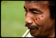 Portrait of Kanamari man w/ face paint playing flute in tribal village of Tres Unidos, Amazonas Brazil