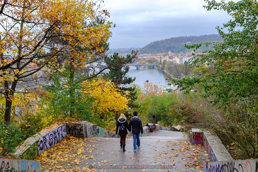A couple make their way down the hill from Letná Park towards the Vltava River and the Old Town of Prague, Czech Republic on 10 November 2014.