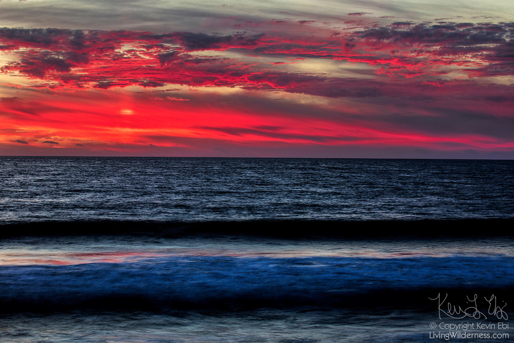 The setting sun reddens low-level clouds, creating a fiery sunset over Pacific Ocean waves as they crash into Venice Beach in California.