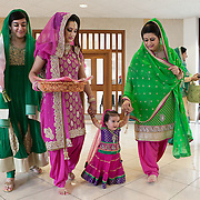 Hounslow, Greater London, UK, January 25, 2015. Sikh Temple Gurdjwara Sri Guru Singh Sobha.<br /> Gurmeet, Ashreena's mother, (dressed in pink) together with Amreet and Mandish (respectively her sister-in-law and mother-in-law), accompany the little girl towards the religious celebration of her first birthday. Unlike what usually happens in the Indian community, where even today daughters are not celebrated, Gurmeet and her husband Sandeep, decided to give a big party for wishing a happy birthday to their daughter and for blessing girls in general.