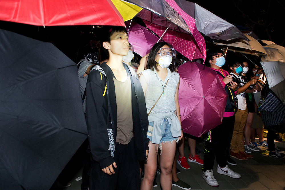 Tense confrontation on Tamar park next to HK government offices. Demonstrators facing police forces and using umbrellas to be protected against pepper spray<br /> <br /> 17th day of pro-democracy protest in Hong Kong