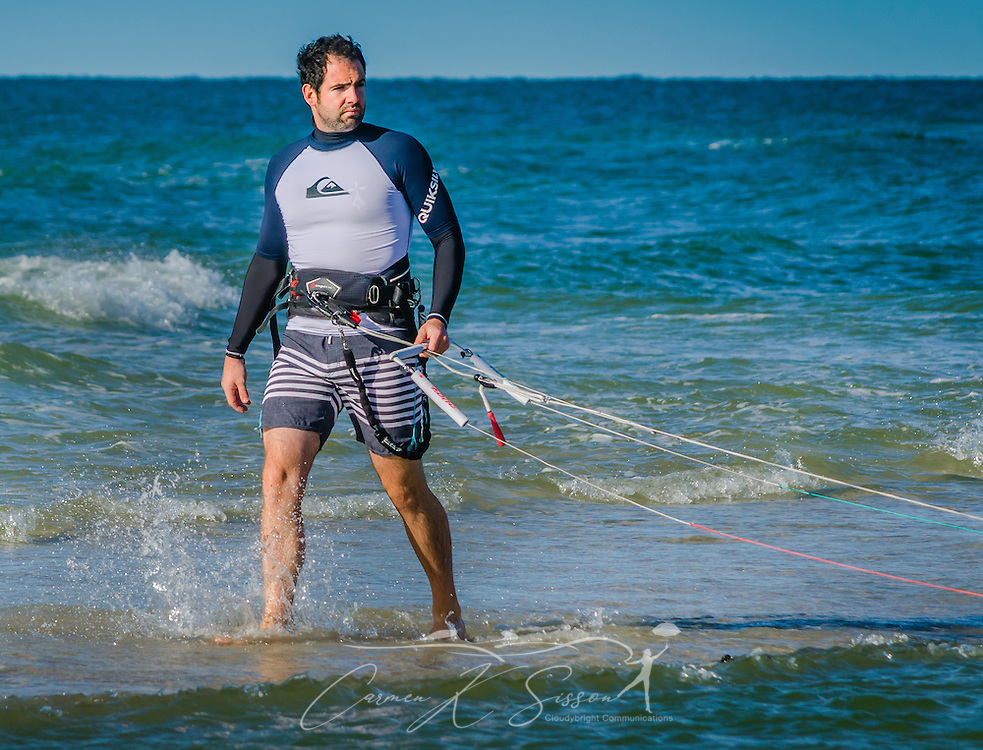 Mathieu Junco looks toward his assistant onshore as he waits to give the signal to launch his F-One Bandit Six kite, October 18, 2015, in Dauphin Island, Alabama. Junco, from France, began kitesurfing five years ago. Windy conditions on the island brought surfers out in droves, but many, like Junco, found that the brisk northerly winds made kitesurfing challenging on the south side of the island. Kitesurfing began in France in the 1980's and became a mainstream water sport in 1999, combining aspects of wakeboarding, windsurfing, surfing, and paragliding. More than 1.5 million people participate in the global sport. (Photo by Carmen K. Sisson/Cloudybright)