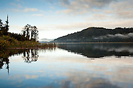 Overcast skies and morning fog  provide reflections on Lake Ianthe on New Zealand's South Island.