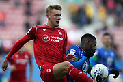 Nottingham Forest defender Joe Worrall (4) clears from Wigan Athletic forward Gavin Massey (11) during the EFL Sky Bet Championship match between Wigan Athletic and Nottingham Forest at the DW Stadium, Wigan, England on 20 October 2019.