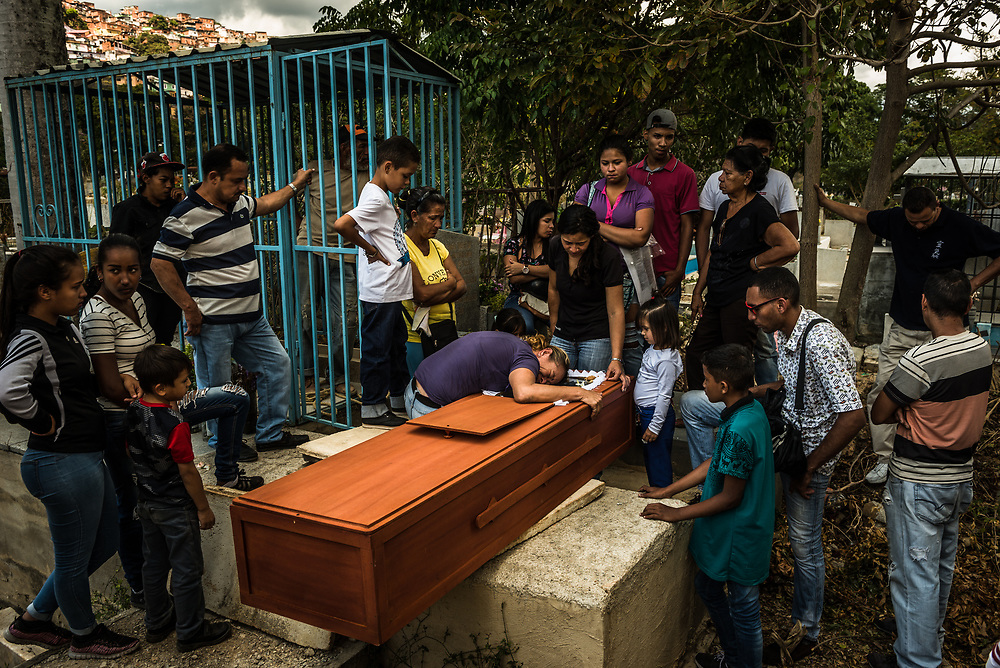 "CARACAS, VENEZUELA - FEBRUARY 25, 2018: Family and friends attend the graveside funeral and burial of Jesús Contreras, 29, who died from tuberculosis at the Dr. José Ignacio Baldó Hospital. After a Catholic priest conducted burial rites, family and friends gathered around his coffin, many in tears - to say goodbye. His grandmother placed a red rose near his face, and his sister placed a cookie, because he always requested them while in the hospital.  His mother, Xiomara Serrano knelt down and hugged his coffin sobbing uncontrollably. As cemetery workers lowered the coffin into the Contreras family tomb, his friends placed a radio on the edge of his grave - blasting salsa and reggaeton music. People hugged and sang along to the lyrics of the last song – by Marco Antonio Solis: ""La gente pasa y pasa siempre tan igual. El ritmo de la vida me parece mal. Era tan diferente cuando estabas tú, si que era diferente cuando estabas tú,"" they sang. ""People pass by and pass by always the same. The rhythm of life seems bad to me. It was so different when you were here, yes it was different when you were here."" PHOTO: Meridith Kohut for The New York Times"