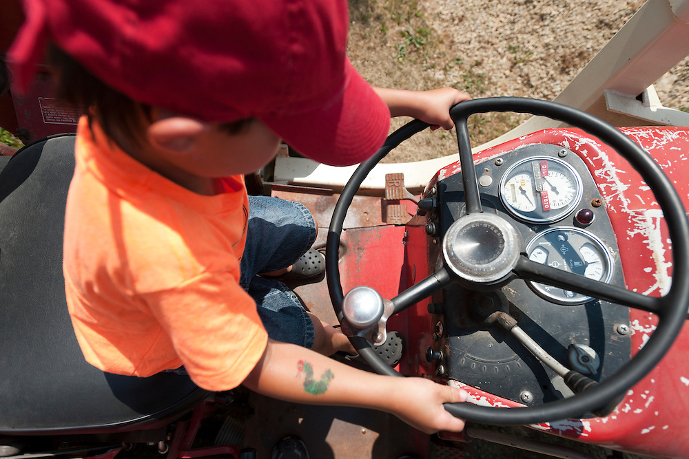 Holden Miller, 5, pretends to drive an International Harvester tractor during the fourth annual International Student Farm Outing at the Schultz Family Farm in Cottage Grove, Wis., on June 24, 2012. Co-sponsored by the Schultz family and the University of Wisconsin-Madison International Student Services (ISS), the event introduced more than 100 UW-Madison international students and their families, and friends of the Schultz family to agricultural life in rural Wisconsin.