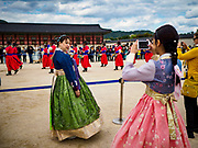 "10 OCTOBER 2018 - SEOUL, SOUTH KOREA:  At Gyeongbokgung Palace wear ""Hanbok"" style clothing. Hanbok is traditional Korean clothing, originally popular in the late Joseon dynasty, before the Japanese conquest of Korea. It is known for vibrant colors and simple lines without pockets. The term literally means ""Korean clothing"", but hanbok usually refers specifically to clothing of the Joseon period. The South Korean government encourages people to wear Hanbok clothing to festivals and cultural celebrations and some museums give free admiccion to people wearing Hanbok clothing.       PHOTO BY JACK KURTZ"