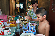 """Mar. 19, 2009 -- BANGKOK, THAILAND: A boy picks condiments for his lunch in a neighborhood food stall in the Ban Krua section of Bangkok. The Ban Krua neighborhood of Bangkok is the oldest Muslim community in Bangkok. Ban Krua was originally settled by Cham Muslims from Cambodia and Vietnam who fought on the side of the Thai King Rama I. They were given a royal grant of land east of what was then the Thai capitol at the end of the 18th century in return for their military service. The Cham Muslims were originally weavers and what is known as """"Thai Silk"""" was developed by the people in Ban Krua. Several families in the neighborhood still weave in their homes.   Photo by Jack Kurtz"""