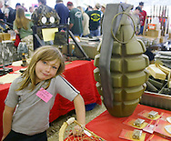 A girl mans a booth selling empty grenades during the Knob Creek Machine Gun Shoot near West Point, Kentucky April 10, 2005. Thousands of machine gun and military hardware enthusiasts attended the event held each year over weekends in the spring and fall.