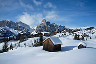 Two snow covered wooden barns at the Alta Badia ski resort near Corvara in the Dolomites.Mount Sassongher is in the distance.  South Tyrol, Italy