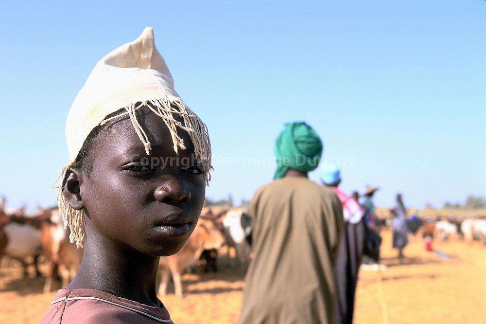 Jeune berger peul semi nomade, ayany amene ses troupeaux de zebus pour -la traversee des vaches-. La fete de la traversee des vaches est l'une des fetes peules les plus importantes du Mali. Elle marque de ladebut de la transhumance, lorsque les traversent le fleuve Niger pour changer de rive, a la fin du mois de novembre. Jeune berger peul semi nomade, ayany amene ses troupeaux de zebus pour -la traversee des vaches-. La fete de la traversee des vaches est l'une des fetes peules les plus importantes du Mali. Elle marque de ladebut de la transhumance, lorsque les traversent le fleuve Niger pour changer de rive, a la fin du mois de novembre./ FRANCE ONLY