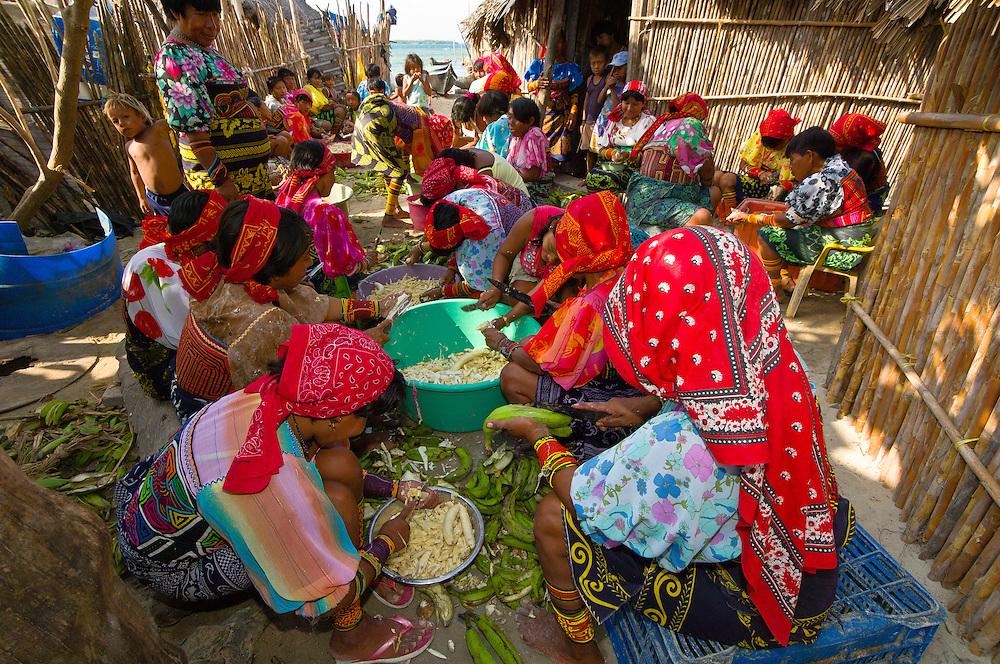 Kuna Indian women wearing native costumes with Mola embroderies cutting up bananas in their village on Corbisky Island, San Blas Islands (Kuna Yala), Caribbean Sea, Panama