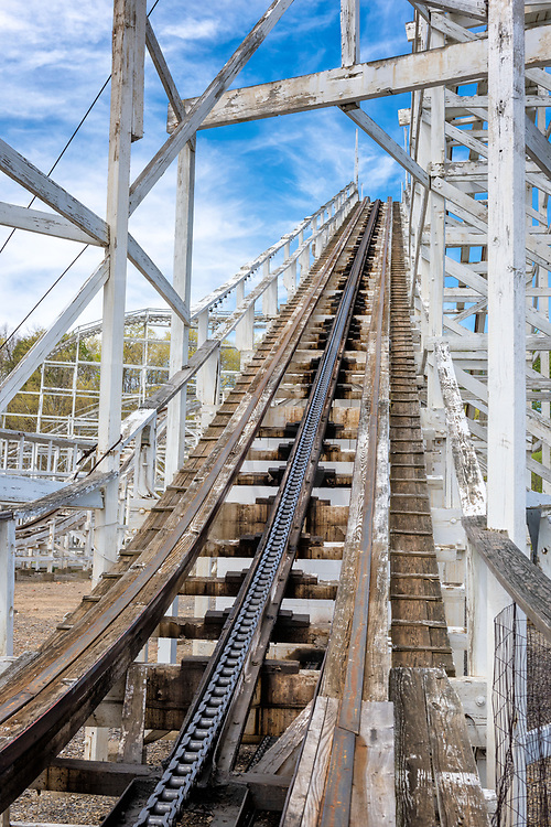 The uphill climb on an on an old fashioned wooden roller coaster at Lakemont Park in Altoona PA, with the incline leading to a fair weather blue sky.