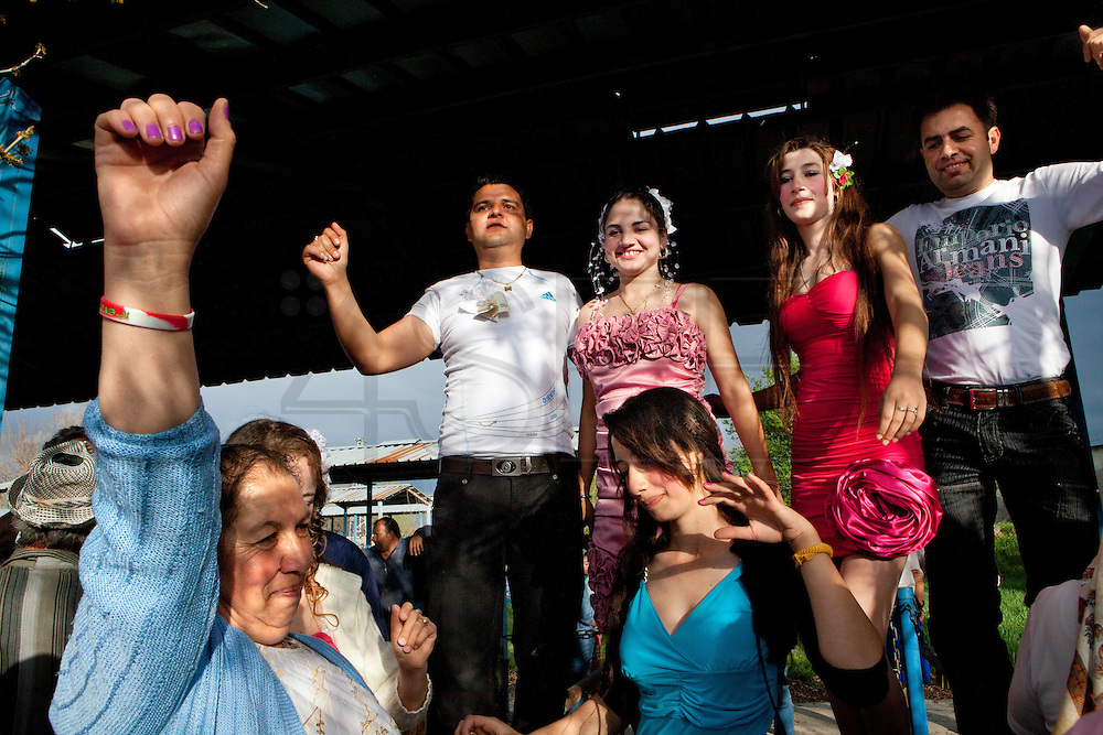Parents and relatives celebrates a wedding dancing. Each spring in Mogila, Bulgaria, is celebrated the Gypsy Bride Market. In this festival the virginity is for sale. The honor can be bought. Every girl has a price to be agreed between the parents of the girl and the candidate. The price can range between 1.500 and 10.000€, in a country where the minimum salary is just over 100€. The market joins the Kalajdzii families, known as the thracians tinkerers, whose tradition is still alive. Many girls dress as real princesses, others prefer to dress in a modern way. They dance during hours the ring dance while grandparents and parents watch the way the young interrelate. Many girls dream to be married by the rite imposed by the tradition. Nowadays there are some girls that don't agree with the tradition and would prefer not to marry, although they assist to these market all the times. Divorces and elopements, so far taboo, are becoming everytime more frequent. Beyond the topic, ethnologists, define it as the Kalajdzii's disco, where the family honor is involved in a commercial transaction. This ritual has being celebrated for years, so anthropologists think is not going to change too much in future.