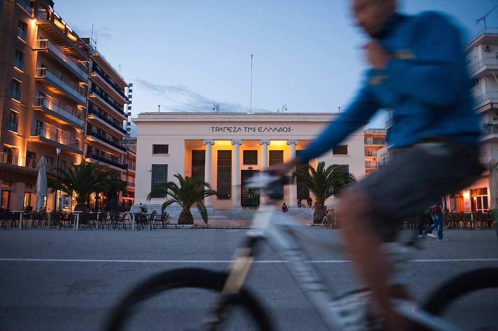 People cycling in front of the Bank of Greece building in the seafront of Volos.