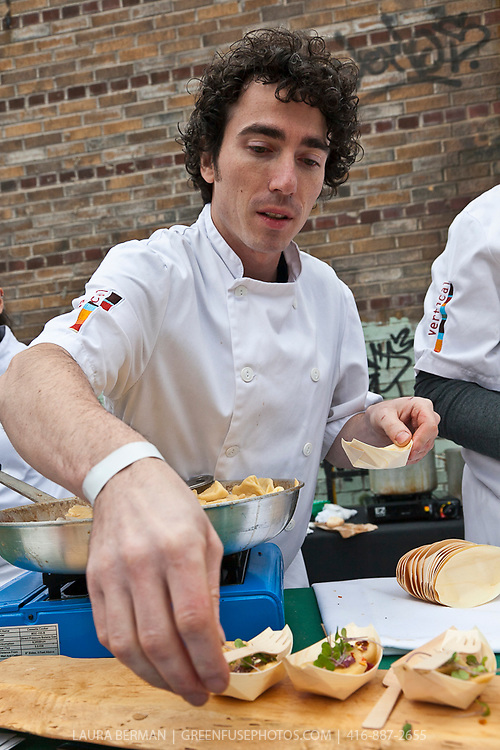 A chef places small portions of food into little wooden serving boats at Slow Food's Picnic at the Brick Works in Toronto, 2010..