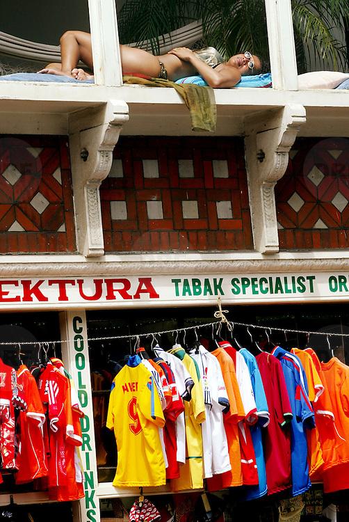 Nederland Amsterdam 17 juli 2005 20050717 Foto: David Rozing .Een allochtone vrouw geniet liggend in haar raamkozijn aan een winkelstraat van het zonnige weer.Foto David Rozing