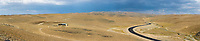 panoramic view of desert or scrub with road and small farm building. large format image file suitable for backdrops or film or TV translights.