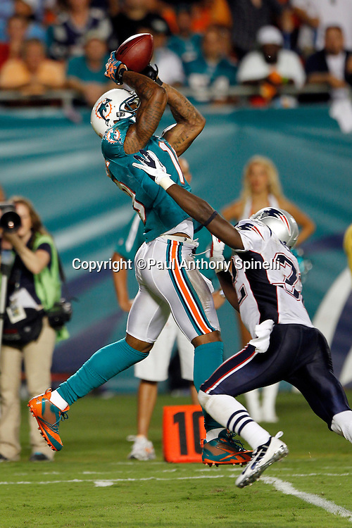 Miami Dolphins wide receiver Brandon Marshall (19) leaps and catches a third quarter pass inside the five yard line while covered by New England Patriots defensive back Devin McCourty (32) during the NFL week 1 football game against the New England Patriots on Monday, September 12, 2011 in Miami Gardens, Florida. The Patriots won the game 38-24. ©Paul Anthony Spinelli