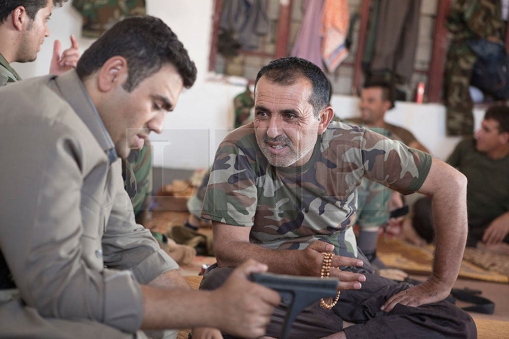 © Licensed to London News Pictures. 01/09/2015. Bashiqa, Iraq. Kurdish peshmerga chat between guard shifts inside their accommodation on the top of the Bashiqa Mountain near Mosul, Iraq.<br /> <br /> Bashiqa Mountain, towering over the town of the same name, is now a heavily fortified front line. Kurdish peshmerga, having withdrawn to the mountain after the August 2014 ISIS offensive, now watch over Islamic State held territory from their sandbagged high-ground positions. Regular exchanges of fire take place between the Kurds and the Islamic militants with the occupied Iraqi city of Mosul forming the backdrop.<br /> <br /> The town of Bashiqa, a formerly mixed town that had a population of Yazidi, Kurd, Arab and Shabak, now lies empty apart from insurgents. Along with several other urban sprawls the town forms one of the gateways to Iraq's second largest city that will need to be dealt with should the Kurds be called to advance on Mosul. Photo credit: Matt Cetti-Roberts/LNP